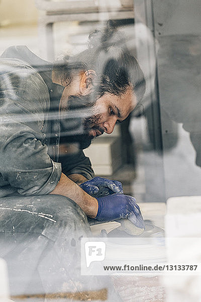 Craftsman using pottery wheel while making earthenware in workshop seen through window