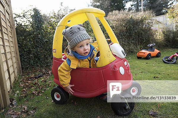 Mädchen fährt Spielzeugauto im Hinterhof