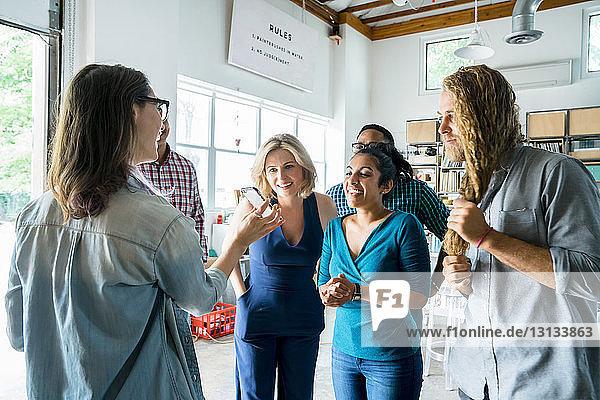 Weibliche Kollegin zeigt Geschäftsleuten ein Smartphone