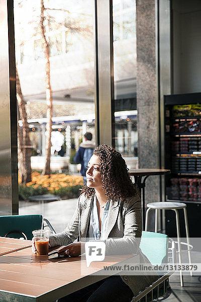 Nachdenkliche Geschäftsfrau sitzt am Café-Tisch