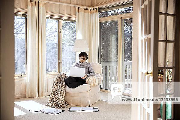 Ältere Frau benutzt Laptop  während sie zu Hause auf einem Sessel sitzt