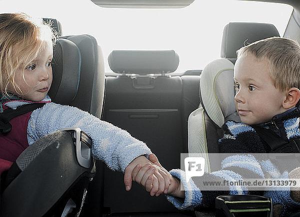 Geschwister  die im Auto sitzen und dabei Händchen halten