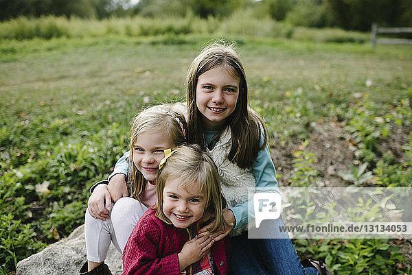 Porträt von fröhlichen Schwestern auf dem Feld im Park