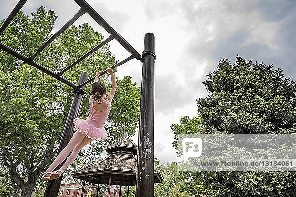 Rear view of girl in ballet costume hanging on monkey bars against cloudy sky at playground
