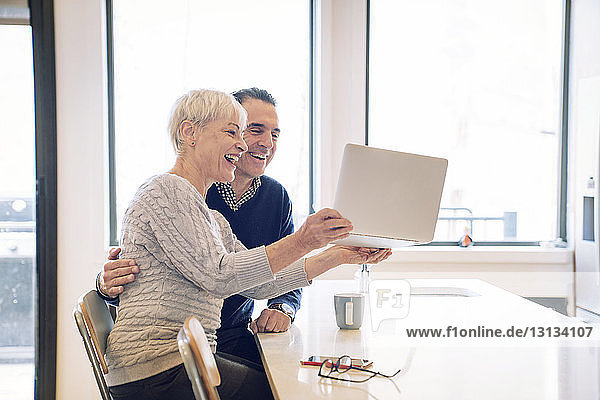 Happy senior woman holding laptop computer while sitting by man at table