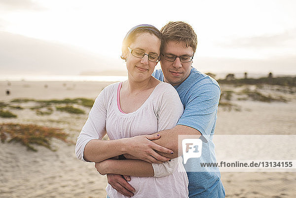 Man embracing woman while standing at beach