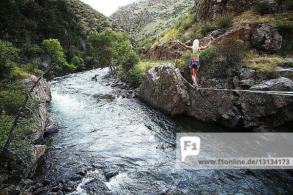 Rückansicht einer Frau  die über einen Fluss gegen Berge slackt