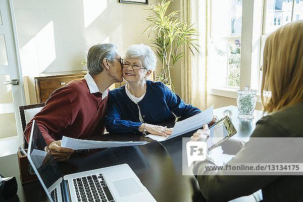 Älterer Mann küsst ältere Frau  während er im Büro eines Finanzberaters sitzt