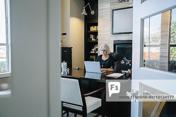Geschäftsfrau  die am Laptop-Computer am Schreibtisch im Büro arbeitet  durch die Tür gesehen
