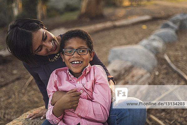 Happy mother with son sitting in forest during sunset