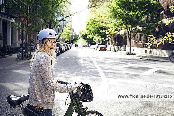 Seitenansicht Porträt einer glücklichen Frau mit Fahrrad auf der Straße