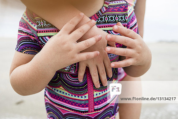 Cropped hand of girl on sister's chest at beach