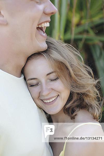 Glückliches junges Paar umarmt sich am Strand