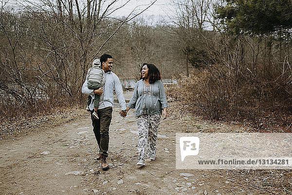 Vater trägt seinen Sohn  während er mit seiner Frau auf einer Straße im Wald spazieren geht