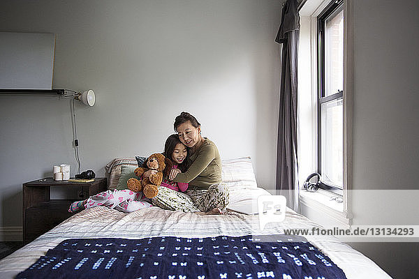 Mother embracing daughter while sitting on bed at home