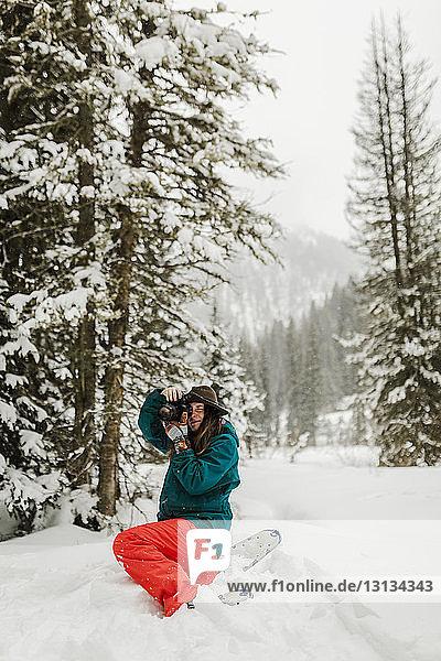 Frau fotografiert mit der Kamera  während sie auf einem schneebedeckten Feld im Wald kauert