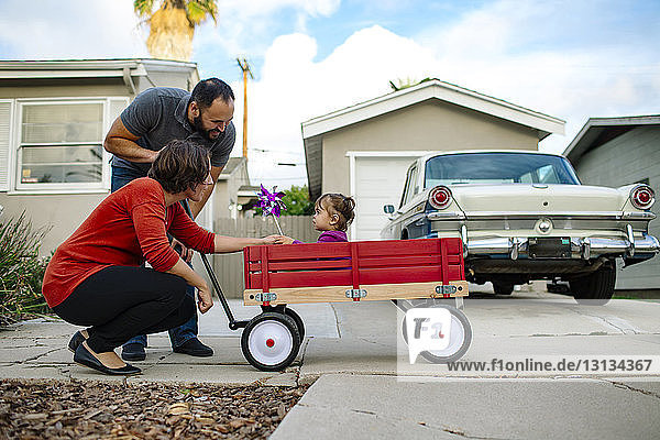 Father and mother looking at daughter sitting in toy wagon