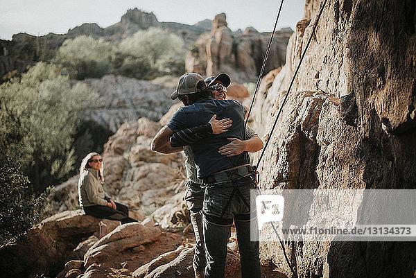 Frau schaut auf männliche Freunde  die eine Felsformation im Red Rock Canyon National Conservation Area umarmen