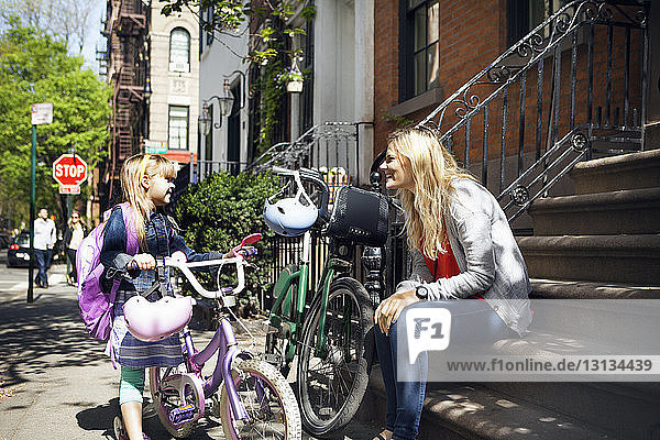 Happy woman talking to daughter while sitting with bicycles on steps