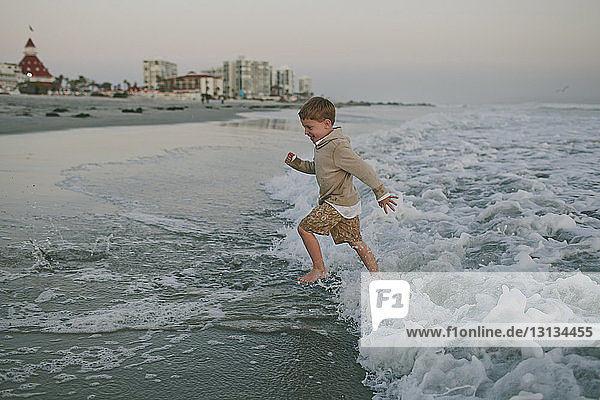 Side view of playful boy running on shore
