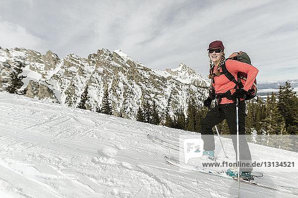 Glückliche Frau mit Himmel geht auf schneebedecktem Berg gegen wolkigen Himmel im Wald