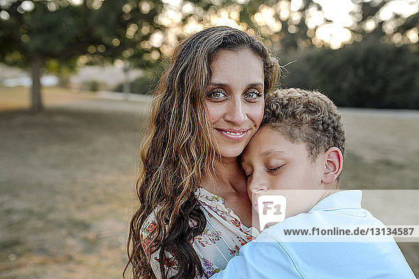 Portrait of loving mother embracing son at park