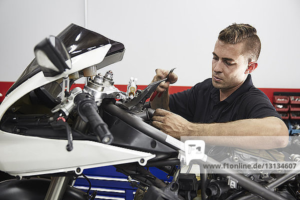 Worker repairing motorcycle in workshop