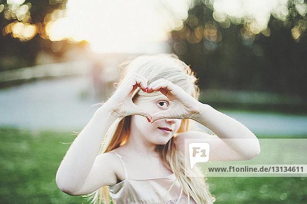 Porträt eines Mädchens  das im Park aus Händen ein Herz formt