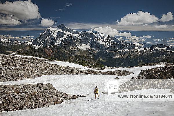 Mitteldistanzansicht einer Wanderin  die im Winter im North Cascades National Park auf Schnee gegen Berge und bewölkten Himmel steht