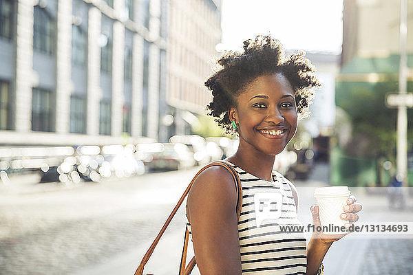 Porträt einer glücklichen Frau  die einen Einwegbecher auf der Straße der Stadt hält