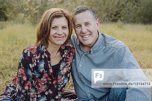 Porträt eines lächelnden Paares  das auf einem Feld im Park sitzt