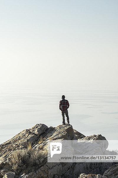 Rückansicht eines Menschen  der auf das Meer schaut  während er auf einem Felsen gegen den Himmel steht