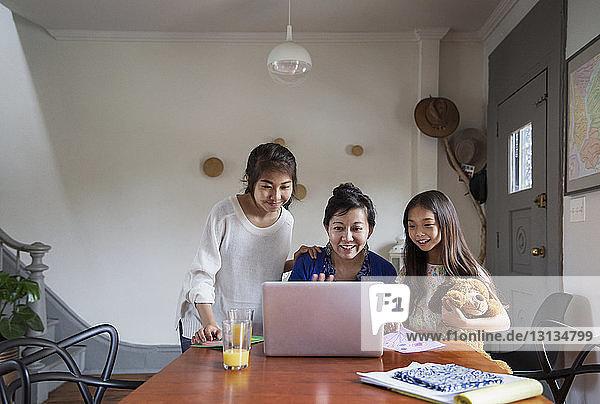Glückliche Familie schaut zu Hause auf den Laptop auf dem Tisch