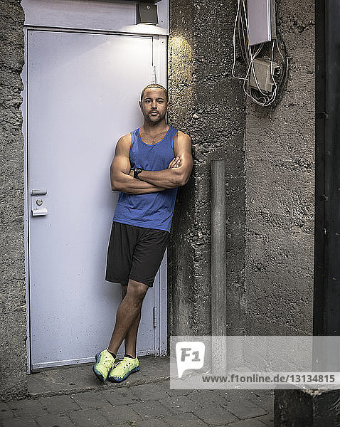 Portrait of man with arms crossed leaning by doorway