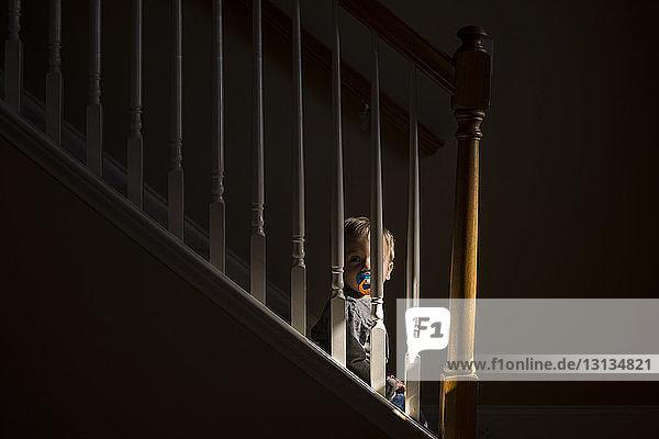 Junge mit Schnuller im Mund schaut weg  während er zu Hause auf Stufen sitzt