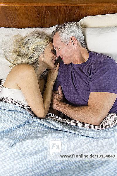 Schrägansicht eines liebenden Paares  das zu Hause auf dem Bett zusammen schläft
