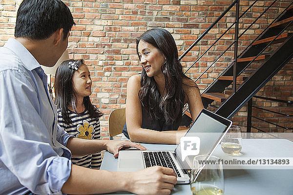 Eltern schauen Mädchen an  während sie am Tisch sitzen