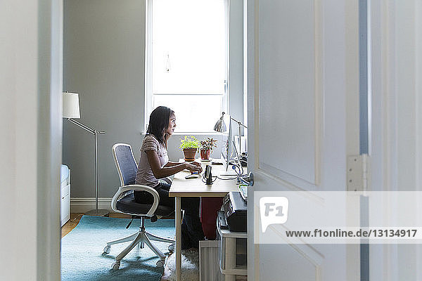 Frau  die am Desktop-Computer im Heimbüro arbeitet  durch die Tür gesehen