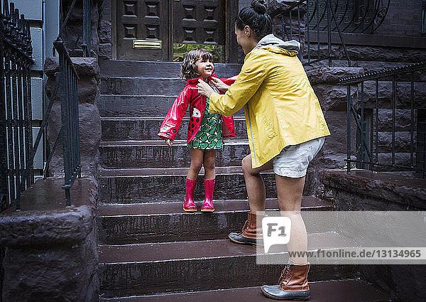 Mutter zieht der Tochter den Regenmantel auf der Treppe aus