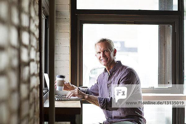 Porträt eines lächelnden reifen Mannes  der eine Kaffeetasse hält  während er seinen Laptop am Tisch im Café benutzt