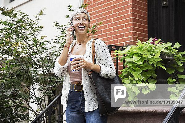 Glückliche Frau telefoniert mit einem Mobiltelefon  während sie eine Kaffeetasse hält