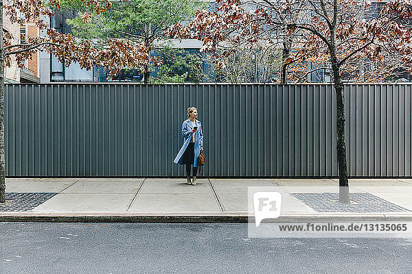 Full length of young woman wearing trench coat while standing against corrugated iron at sidewalk in city