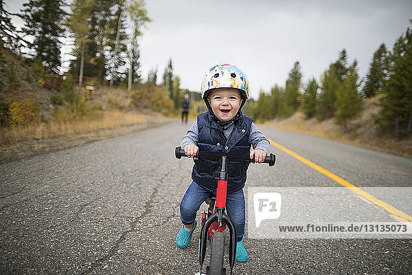 Portrait of cute cheerful baby boy riding bicycle on country road
