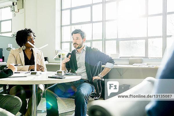 Geschäftsleute diskutieren über Windmühlenmodelle  während sie im Büro am Schreibtisch sitzen