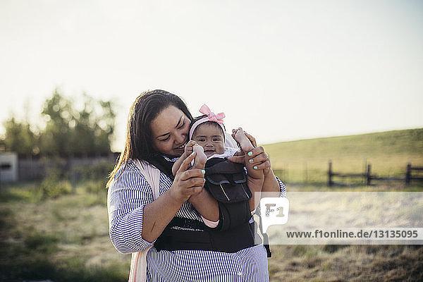 Glückliche Mutter spielt mit ihrer Tochter  während sie auf der Ranch vor dem klaren Himmel steht