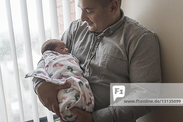 Vater trägt neugeborenen Sohn  während er im Krankenhaus am Fenster steht