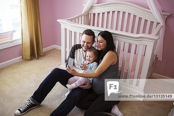 Schrägaufnahme einer Familie  die Selbsthilfe nimmt  während sie zu Hause vor dem Kinderbett sitzt