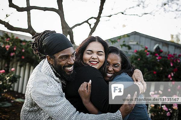 Glückliche Familie umarmt  während sie im Park vor dem klaren Himmel steht