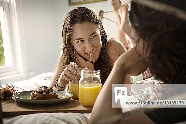 Young woman looking at boyfriend while having breakfast
