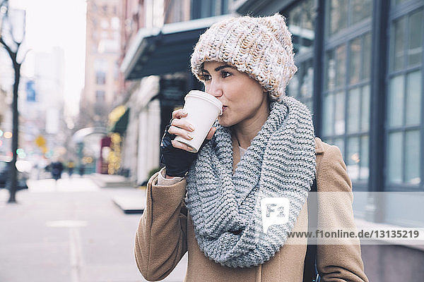 Woman enjoying drink while standing on city street